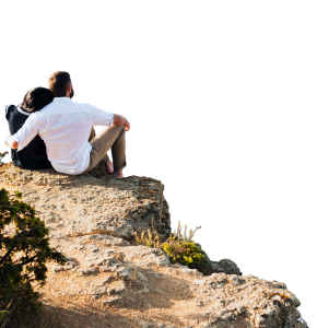 Couple sitting on a cliff looking out at a wedding marquee